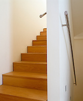 This contemporar wooden staircase is fitted with a stainless steel hand rail