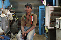 A boy sits outside his family's store in the Chandni Chowk electronics market in Kolkata, India. November, 2013