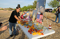 """Gilbert, Arizona – Friends and family of the Mederos Family gathered to hold a memorial for the four victims of the Gilbert Massacre occurred on May 2, 2012. According to Gilbert Police, Lisa Mederos, Amber Mederos, baby Lilly Mederos, and Jim Hiott (Amber's fiancé) were all killed by notorious white supremacist and Neo-Nazi Jason """"J.T."""" Ready before taking his own life. In this image, a high-school friend of victim Amber Mederos pays his respects by bringing flowers to the memorial. Amber's friend did not want to provide his name, but said they attended together Mesquite High School, in Gilbert, where the massacre occurred.. Photo by Eduardo Barraza © 2012"""