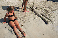 Spain. Mallorca in the Balearic islands. Colonia Sant Jordi. A father and his daughter play on the beach. They have carved a woman figure in the sand. © 1999 Didier Ruef