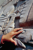A blind person touches a detail from the stone depicting Coyolxauqui the moon goddess at the Templo Mayor in Mexico City during a tour offered for blind people.