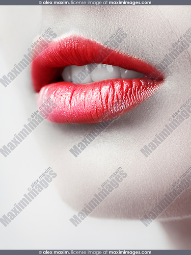 Closeup of young woman lips, slightly open mouth and red lipstick. Artistic black and white with red.