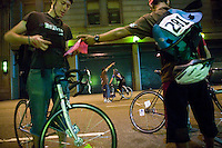 3 July 2005 - New York City, NY, USA - &quot;Junjun&quot; (R, foreground) and Richard (2L, background) stamp riders' manifests at an alleycat checkpoint on 43rd street in New York City, USA, July 3rd 2005. Alleycats are urban cycle races held informally - without notification of the authorities - on open roads and in real traffic, to simulate the messenger's working conditions. Photo Credit: David Brabyn<br />