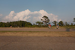 Bicyclists on the Colonial Parkway at College Creek and the James River Virginia. Summer  clouds tower over the landscape NO MODEL RELEASE