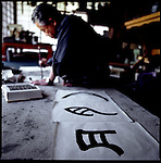 "Kawamata-sensei renders kanji (Chinese characters) in his studio in Mito, Japan.  Several versions in the evolution of the character ""tsuki"", or moon, extend away from Kawamata-sensei into the foreground."