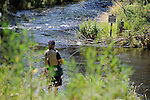 Fly fisherman on the Fall River in Oregon near posted no trespassing sign.