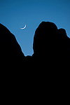 Indian Cove Campground, Joshua Tree National Park, Twenty Nine Palms, California; a sliver of a moon setting over the rock formations at twilight