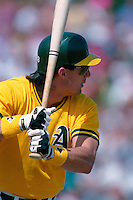 PHOENIX, AZ - Jose Canseco of the Oakland Athletics bats during a spring training game against the San Francisco Giants at Phoenix Municipal Stadium in Phoenix, Arizona in 1992. Photo by Brad Mangin