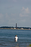 Fisherman, angler, wade fishing with the Bolivar Lighthouse in the background, at East Beach, Galveston.