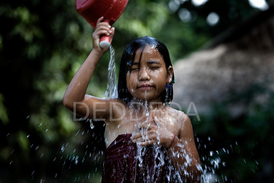 A young girl bathes with a water basin in a rural village near Luang Prabang, Laos.