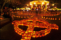 Hundreds of bright faralitos, each a paper bag containing a candle, form a Zia symbol during the Christmas Eve celebration on the plaza in Old Town in Albuquerque, New Mexico