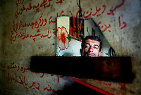 A worker from the Gaddani ship-breaking yard reflected in a shard of broken mirror in his living quarters.