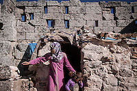 "In this Friday, Sep. 27, 2013 photo, a Syrian displaced mother brushes her daughter's hair outside their family stone house at the Kafr Ruma, an ancient roman ruins used as temporary shelter by those families who have fled from the heavy fighting and shelling in the Idlib province countryside of Syria. Dozens of families settled in the ancient ruins known as ""The Forgotten City"" and declared human heritage by UNESCO, when the clashes between opposition fighters and government forces broke out in the region since more than two years ago. (AP Photo)"