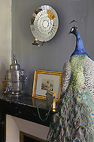 "On the mantlepiece of the ""Peau d'ane"" room, and lit by a a mirrored sconce,  sits a stuffed peacock, a gilt-framed print, an antique handbag and a silver samovar"