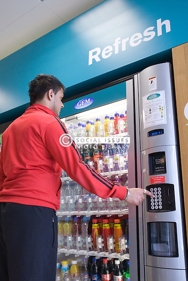 Young man buying a drink from the chilled vending machine at his sports leisure centre,