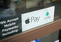 Signage in the window of a drug store in New York informs shoppers of their acceptance of both Apple Pay and Android Pay mobile payments systems, seen on Thursday, April 28, 2016. (© Richard B. Levine)
