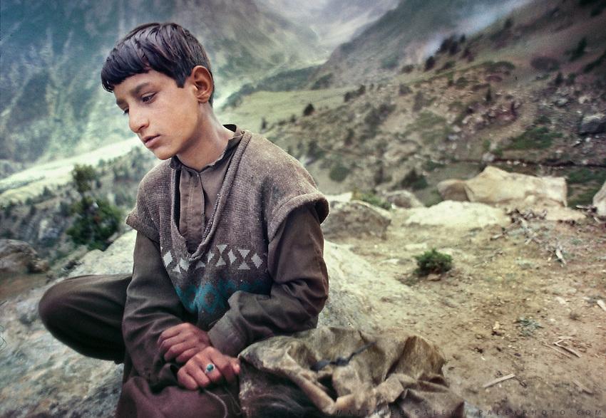 A young shepherd takes a break at his high altitude pasture. Trekking in Basho Valley..Karakoram mountain range, Baltistan, Pakistan.