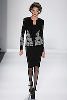 Model walks runway in a black doublefaced wool crepe princess cardigan bordered w/black+ivory reembroidered french lace+sheath dress, from the Zang Toi Fall 2012 &quot;Glamour At Gstaad&quot; collection, during Mercedes-Benz Fashion Week New York Fall 2012 at Lincoln Center.