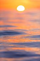 A close focus image of the calm ocean reflecting a sunset near Maui.