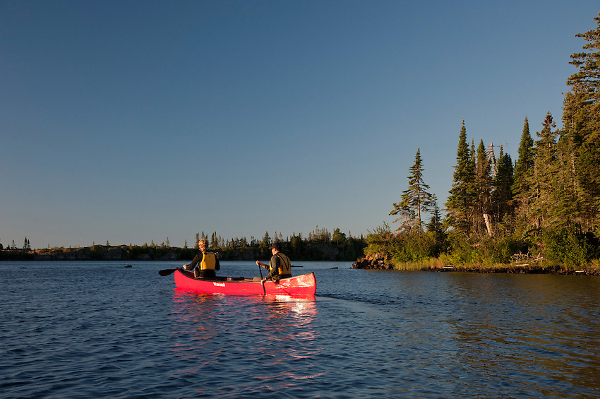 A couple paddles a red canoe on Merritt Lane at Isle Royale National Park in Michigan USA.