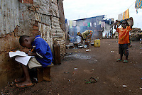 Kroo Bay, Freetown, Sierra Leone...Story on child and maternal health in the Kroo Bay slum community in Freetown, Sierra Leone, which has the World's worst infant and maternal mortalitly rates. One in 4 children die before they reach the age of 5 and one in 6 mothers dies during child birth (in the UK, the rate is one in 3,800)...The Kroo Bay Community Health Centre has a catchment area of over 8,000 people but lacks adequate facilites to provide even basic care. The clinic lacks even the basics, such as bedpans, surgical spirits and cotton wool. It has no electricity and clean drinking water must be fetched from the nearby well everyday...Dauda Turay (12), who attends the nearby FAWE school, does his english homework after coming home from school...© 2007 Aubrey Wade. All rights reserved.