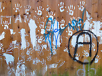 Switzerland. Canton Ticino. Lugano. Graffiti on a wooden wall. Anarchy sign. Fingers and hands' palms. 10.04.13 © 2013 Didier Ruef