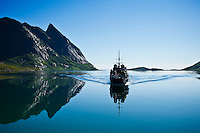 Tourist ferry travel through fjord to Vindstad, Lofoten islands, Norway