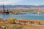 Along the shores of the Hillcrest Reservoir, a southbound BNSF freight train rolls down the Front Range Subdivision next to the Valmont Power Plant with the snow capped peaks of the Rocky Mountains in the distance.