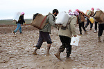SHILAKAY, IRAQ: Syrian smugglers--one shoeless--begin the 4 hour walk from Iraq into Syria...Due to the recent conflict in Syria there is a gasoline shortage in the country. Syrian smugglers purchase gasoline in Iraq and smuggle it into Syria for a profit of about $0.40 per liter. Smugglers carry between 10 and 30 liters per person on the 7 hour roundtrip journey that often takes them through frozen mud and snow...Photo by Aram Karim/Metrography