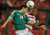 MEXICO CITY, MEXICO - AUGUST 15, 2012:  Fabian Johnson (23) of the USA MNT heads the ball with Andres Guardado (18) of  Mexico during an international friendly match at Azteca Stadium, in Mexico City, Mexico on August 15. USA won 1-0.