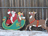 A vintage plywood cutout of Santa followed by a reindeer rest against a wood and chain link fence in the winter snow.