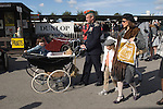 "Goodwood Festival of Speed. Goodwood Sussex. UK. Retro dressing man. Neil Reynolds 48yrs old  pushing a 1957 Marmet pram with daughter 5 yr oldf Pipper. He is wearing his fathers 23rd Hussars officers uniform. His 6th revival. ""They get better everytime."""