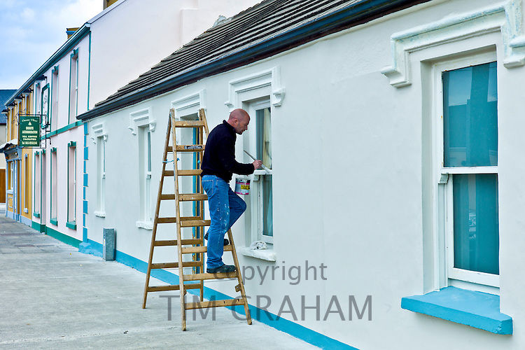 Man paints windows of a house in Chapel Street, Kilkee, County Clare, West of Ireland
