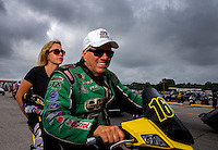 Aug 31, 2014; Clermont, IN, USA; NHRA funny car driver John Force on his scooter with daughter top fuel dragster driver Brittany Force during qualifying for the US Nationals at Lucas Oil Raceway. Mandatory Credit: Mark J. Rebilas-USA TODAY Sports