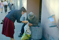 Saint Petersburg, Russia, August 2002..A woman pauses on Nevsky Prospect to give a homeless man a loaf of bread. Fyodor Dostoyevsky,  chronicler of Russia's under class, would still recognise much in his native city. The streets he knew still teem with thieves, drunks, homeless &amp; those on the fringes of society..