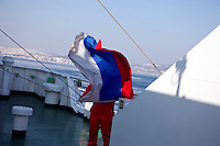 An employee of the Eastern Dream ferry holds a Russian flag as the ferry arrives at the port of Vladivostok.