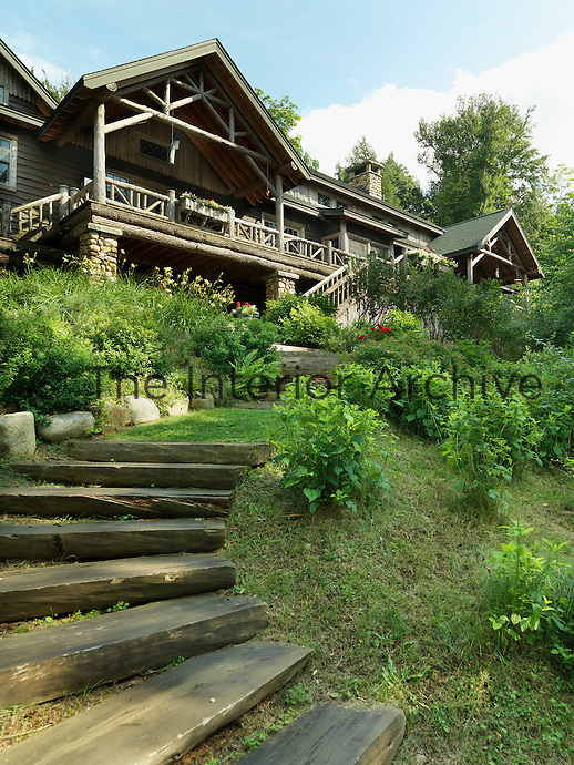 Wooden steps wind up through the garden to the log cabin built in the vernacular Adirondack-style