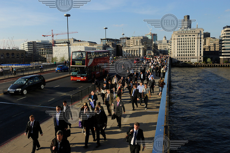 Commuters crossing London Bridge over the River Thames, with the City behind them.