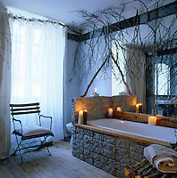 A rustic bath clad in granite slabs in a room which is decorated with winter branches and lit with an array of candles