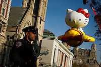 "A New York Police officer stands guard while the ""Hello Kitty"" balloon is seen during the 89th Macy's Thanksgiving Annual Day Parade in the Manhattan borough of New York.  11/26/2015. Eduardo MunozAlvarez/VIEWpress"