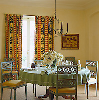 A wrought-iron chandelier hangs over a large vase filled with roses on the table in this mint green and yellow dining room