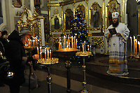The priest performs Christmas mass as a woman lights a candle at the Christmas Church in Odessa, Ukraine on January 7, 2016.  Orthodox Christians around the world celebrate Christmas on January 7.