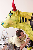 """August 9, 2012. Durham, NC.. Warren Hicks works on his cow, """"The Cow is Greener on the Other Side""""..  Artists from all over the state have been working at Golden Belt decorating their assigned cows for the Parade of Cows, to be held this month. After the cows are displayed around the Triangle, they will be auctioned off to benefit the NC Children's Hospital."""