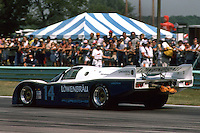 ELKHART LAKE, WI - AUGUST 24: The Holbert Racing Porsche 962 103 of Al Holbert of the United States and Derek Bell of Great Britain is driven toward Turn 5 en route to victory in the Budweiser 500 IMSA GT race at the Road America track near Elkhart Lake, Wisconsin, on August 26, 1984.