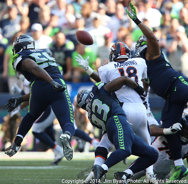Seattle Seahawks defensive end Cliff Avril, (56), defensive tackle O'Brien Schofield (93) and defensive tackle Jordan Hill (97) pressure Denver Broncos quarterback Peyton Manning in the fourth quarter at CenturyLink Field in Seattle, Washington on September 21, 2014. The Seahawks won 26-20 in overtime.    ©2014. Jim Bryant Photo. All rights Reserved.
