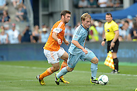 Seth Sinovic (15) defender Sporting KC shields the ball from Will Bruin (12) forward Houston Dynamo in action..Sporting Kansas City and Houston Dynamo played to a 1-1 tie at Sporting Park, Kansas City, Kansas.