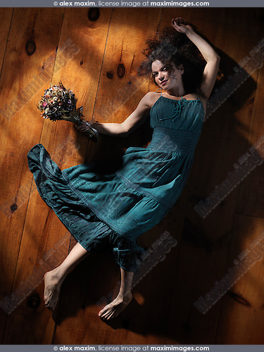 Cute smiling young woman in a green dress lying on the floor with a bouquet of wild flowers and a dreamy look on her face, artistic abstract portrait