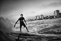 17 year old surfer Amer Aldos rides a wave in the Mediterranean Sea off the shore of Gaza City.