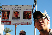 """Phoenix, Arizona. January 19, 2013 - A man listens as several speakers address the crowd during Saturday's rally on Phoenix. In the background, a sign in favor of protecting the Second Amendment includes photos of Joseph Stalin, Mao T'se-tung and Adolf Hitler. As President Barack Obama proposed new gun regulations last week, gun owners demonstrated against it with national """"Guns Across America"""" rallies to defend the Second Amendment. Dozens showed up at the Arizona State Capitol, many of them carrying weapons. Photo by Eduardo Barraza © 2013"""