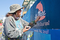 Artist Janet Wallace paints a sign advertising the new Italian restaurant, Al Mare, at the Santa Monica Pier on Tuesday, February 28, 2012. All Mare will open in the Fall.